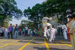 KOLKATA, WEST-BENGALEN, INDIA - MAART EENENTWINTIGSTE 2015: Jonge jongen die in witte kleding van grond over springen aan voorbij stock afbeeldingen
