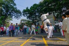 KOLKATA, WEST-BENGALEN, INDIA - MAART EENENTWINTIGSTE 2015: Jonge jongen die in witte kleding van grond over springen aan voorbij royalty-vrije stock afbeeldingen