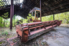 Kolkhoz in Chernobyl Zone. Abandoned combine vehicle in collective farm near Zymovyshche ghost village in Chernobyl Exclusion Zone, Ukraine Stock Images