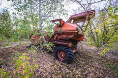Kolkhoz in Chernobyl Zone. Abandoned combine vehicle in collective farm near Zymovyshche ghost village in Chernobyl Exclusion Zone, Ukraine Royalty Free Stock Photo
