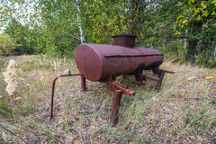 Kolkhoz in Chernobyl Zone. Old tank in collective farm near Zymovyshche ghost village in Chernobyl Exclusion Zone, Ukraine Royalty Free Stock Images