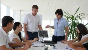 Kollaboratörer som står det near skrivbordet i det vita moderna kontoret, diskuterar möjligheter arkivfilmer