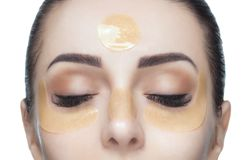 Kollagengoldflecken auf der Haut des Augenlides, der Stirn und des Kinns auf dem Gesicht stockbilder