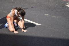Kollapsad maratonlöpare på alla fours, når fullföljande av loppet royaltyfria foton