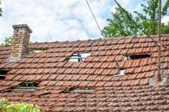 Kollapsat tak med tegelplattor på det gamla förstörda och skadade inhemska huset efter jordskalv- eller orkanstormslut upp royaltyfri foto