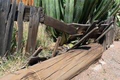 Kollapsat trästaket framme av en gammal övergiven byggnad royaltyfri fotografi