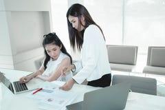 Kollegakvinnamentorn som hjälper den nya arbetaren, undervisande barn, klarar av arkivfoto
