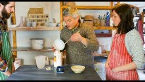 Kollegan som ser konstnären, medan måla på lergods, bowlar stock video