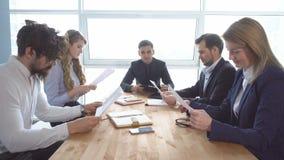 Kollegeblick durch Dokumente Ein Geschäftstreffen Gruppe des jungen Geschäftsmannes am Verhandlungstisch im Büro lizenzfreies stockbild
