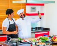 Kollegen bei der Arbeit: Thailändische und europäische Chefs am Küchenhandeln Lizenzfreies Stockbild