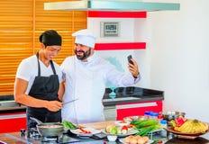 Kollegen bei der Arbeit: Thailändische und europäische Chefs am Küchenhandeln Stockbild