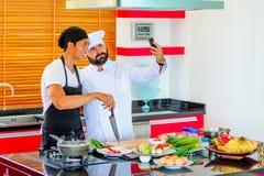 Kollegen bei der Arbeit: Thailändische und europäische Chefs am Küchenhandeln Lizenzfreies Stockfoto