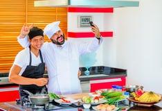 Kollegen bei der Arbeit: Thailändische und europäische Chefs am Küchenhandeln Stockfoto