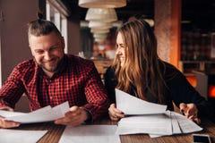 Kollegen besprechen die Dokumente, die in einem Café sitzen Lizenzfreie Stockfotos