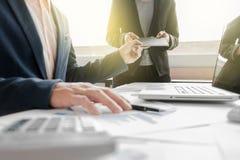 Kollegen des Geschäftsteams zwei, die Finanzdiagramm des neuen Planes besprechen Stockbild