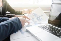 Kollegen des Geschäftsteams zwei, die Finanzdiagramm des neuen Planes besprechen Stockbilder