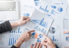 Kollegen des Geschäftsteams zwei, die Finanzdiagramm des neuen Planes besprechen Stockfotografie