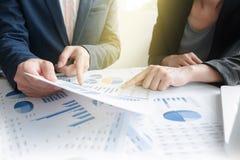 Kollegen des Geschäftsteams zwei, die an Finanzdiagrammdaten besprechen Lizenzfreie Stockfotos