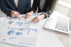 Kollegen des Geschäftsteams zwei, die an Finanzdiagrammdaten besprechen Stockfoto