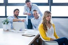 Kollegen, die auf Geschäftsfrau im Büro lachen Stockbilder