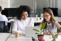 Kollegen, die an der gleichen Aufgabe auf Laptop zusammenarbeiten lizenzfreies stockfoto