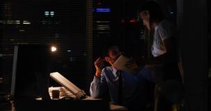 Kollegen, die eine Tablette nachts verwenden stock video footage