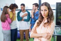 Kollegen, die eine traurige weibliche Exekutive einschüchtern lizenzfreie stockfotos