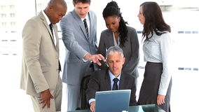 Kollegen, die einem Geschäftsmann mit seinem Laptop helfen Stockfoto