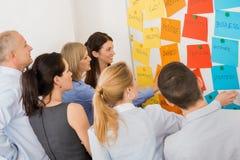 Kollegen, die in Front Of Whiteboard gedanklich lösen Stockfoto