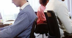 Kollegen, die an Laptop am Schreibtisch arbeiten stock footage
