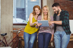 Kollegen, die in Richtung der digitalen Tablette blicken Stockbild
