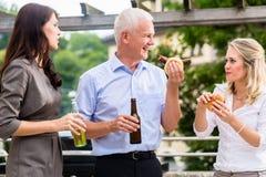 Kollegen, die Würste und Bier nach der Arbeit essen Stockfotos