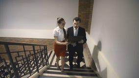 Kollegen gehen die Treppe hinauf und besprechen Projekt stock footage