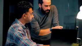 Kollegen mit den Computern, die im Nachtbüro arbeiten stock footage