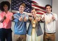 Kollegen mit den Daumen oben gegen amerikanische Flagge Stockfoto