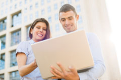 Kollegen mit Laptop in Front Of Company Lizenzfreies Stockbild