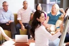 Kollegor för affärskvinnaMaking Presentation To kontor Royaltyfria Bilder