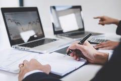 Kollegor för affärslag som två arbetar med datoren, bärbara datorn, att diskutera och handel för analysgrafaktiemarknad med mater arkivfoto