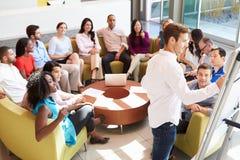 Kollegor för affärsmanMaking Presentation To kontor Arkivfoto