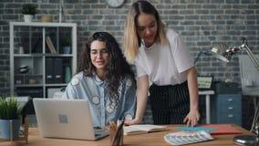 Kollegor för unga damer som talar se bärbar datorskärmen hyr rum i regeringsställning, på skrivbordet stock video
