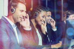 Kollegor med hörlurar med mikrofon genom att använda datoren på kontoret Arkivbilder