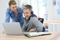 Kollegor på kontoret som arbetar på bärbara datorn arkivbilder