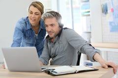 Kollegor på kontoret som arbetar på bärbara datorn royaltyfri bild