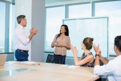 kollegor som applåderar för affärskvinna i konferensrum royaltyfri bild