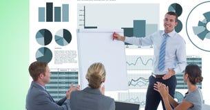 Kollegor som applåderar medan affärsman som ger presentation mot grafer Arkivfoto