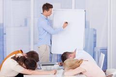 Kollegor som får borrade under affärspresentation Arkivfoto