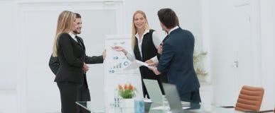 Kollegor som frågar en fråga till en affärskvinna under en gåva arkivfoto