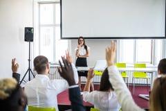 Kollegor som frågar en fråga till en affärskvinna under en presentation Affärskonferens eller utbildning arkivbilder
