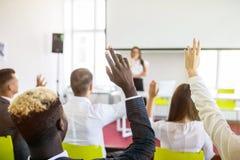 Kollegor som frågar en fråga till en affärskvinna under en presentation Affärskonferens eller utbildning arkivfoto