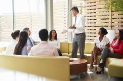 Kollegor som lyssnar till en presentation av en manlig chef royaltyfri bild